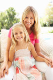 Mother And Daughter Relaxing On Sofa Stock Photography