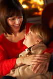 Mother And Daughter Relaxing On Sofa. By Cosy Log Fire Royalty Free Stock Photography