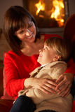 Mother And Daughter Relaxing On Sofa. By Cosy Log Fire Royalty Free Stock Image