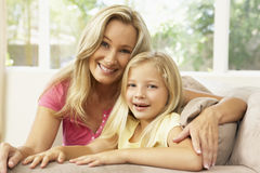 Mother And Daughter Relaxing On Sofa At Home Royalty Free Stock Photography