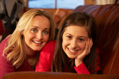 Mother And Daughter Relaxing On Sofa Together Stock Photo