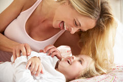 Mother And Daughter Relaxing Together In Bed Stock Photos