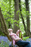 Mother and daughter relaxing on tree trunk in forest Stock Image