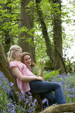 Mother and daughter relaxing on tree trunk in forest Royalty Free Stock Photo