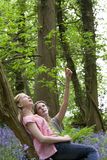 Mother and daughter relaxing on tree trunk in forest Royalty Free Stock Image