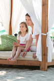 Mother and daughter resting on beach in bed Royalty Free Stock Images
