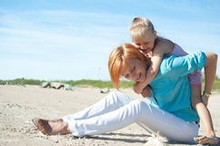 Mother daughter resting beach Stock Photos
