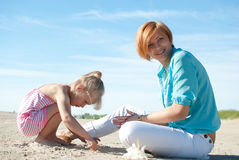 Mother daughter resting beach Stock Images