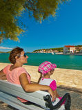 Mother and daughter resting on a bench in a seaside town. Mom and daughter sitting on a bench and look at the sea in Tisno Croatia Stock Photos