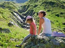 Mother and daughter resting on the big stone at travel excursion. Young mother and cute little daughter resting on the big stone at travel excursion at summer Royalty Free Stock Photo