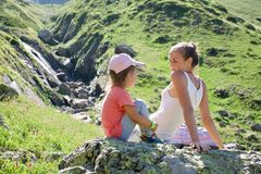Mother and daughter resting on the big stone at travel excursion. Young mother and cute little daughter resting on the big stone at travel excursion at summer Royalty Free Stock Image