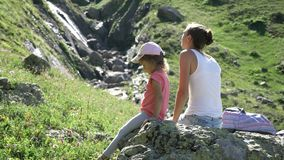 Mother and daughter resting on the big stone at travel excursion. stock video