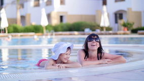 Mother and daughter resting, chatting in the pool stock video