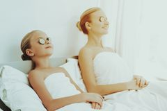 Mother With Daughter Are Resting. Spa Concept. Relaxing Together. Holiday Leisure. Cucumbers On The Eyes. Time To Chill Out. White Body Towels. Smiling Family royalty free stock photos