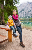 Mother and daughter resting at wooden picnic table on Lake Bries Stock Images