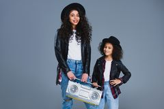 Mother and daughter with retro boombox. Isolated on grey royalty free stock image