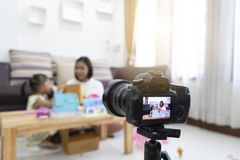 Mother and daughter review playing toys at home. With recording making video stock photo