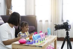 Mother and daughter review playing toys at home. With recording making video royalty free stock photo