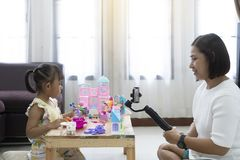 Mother and daughter review playing toys at home. With recording making video royalty free stock image