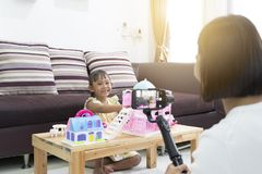 Mother and daughter review playing toys at home. With recording making video royalty free stock photos