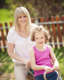Mother and daughter ride seesaw together Royalty Free Stock Photos