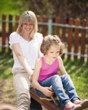 Mother and daughter ride seesaw together Royalty Free Stock Images