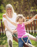 Mother and daughter ride seesaw together Stock Photos