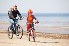 Mother and daughter riding on bicycles Royalty Free Stock Photos