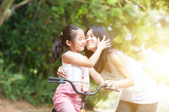 Mother and daughter riding bike and having fun. Stock Photography