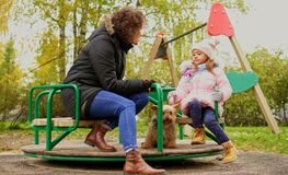 Mother with daughter riding carousel. On a playground Royalty Free Stock Images