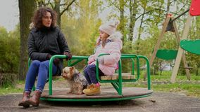 Mother with daughter riding carousel on a playground.  stock video