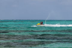 Mother and daughter riding a jet ski. Mother and daughter riding a jet ski in colorful green water, Bahamas Stock Images
