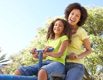 Mother And Daughter Riding On Seesaw In Park Royalty Free Stock Photography