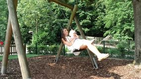 Mother and daughter are riding on a swing stock video footage