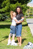 Mother and daughter on roller skates in summer Royalty Free Stock Photo
