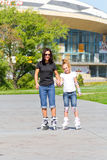 Mother and daughter on roller skates in summer Royalty Free Stock Photos