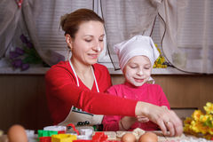 Mother and daughter rolling dough Royalty Free Stock Images