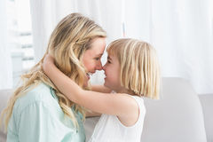 Mother and daughter rubbing noses on sofa Stock Images