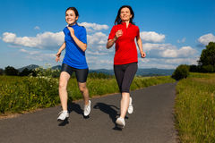 Mother and daughter running Stock Photo