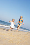 Mother And Daughter Running Along Beach Stock Photography