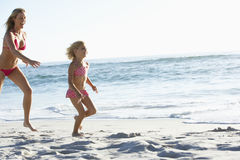 Mother And Daughter Running Along Beach Together Wearing Swimming Costume Stock Images