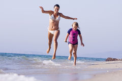 Mother and daughter running at the beach Royalty Free Stock Photos
