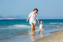 Mother and daughter running on the beach Royalty Free Stock Photo