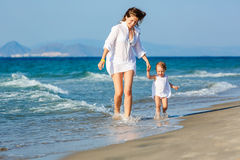Mother and daughter running on the beach Royalty Free Stock Image
