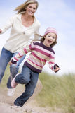 Mother and daughter running on beach smiling royalty free stock photos