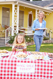 Mother And Daughter Running Charity Bake Sale. Smiling Stock Images