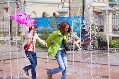 Mother and daughter running through the fountain. Stock Photography