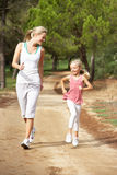 Mother and daughter running in park Royalty Free Stock Images