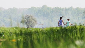 Mother and daughter running on spring field stock video footage
