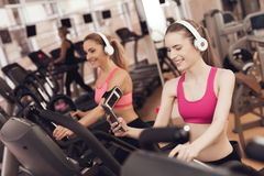 Mother and daughter running on treadmill at the gym. They look happy, fashionable and fit. royalty free stock photos